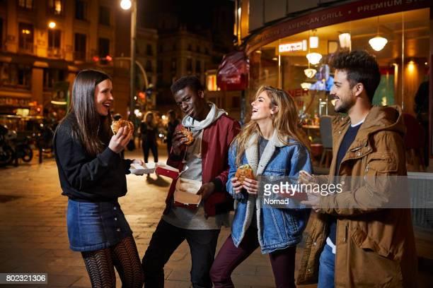 Amis, manger des hamburgers à l'extérieur du restaurant dans la nuit