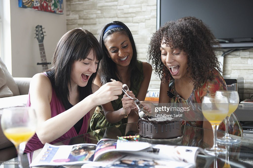 Friends eating cake together in living room : Stock Photo