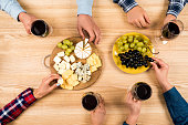 top view of friends eating cheese with grapes and drinking wine at home