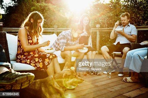 Friends eating dinner together on backyard deck