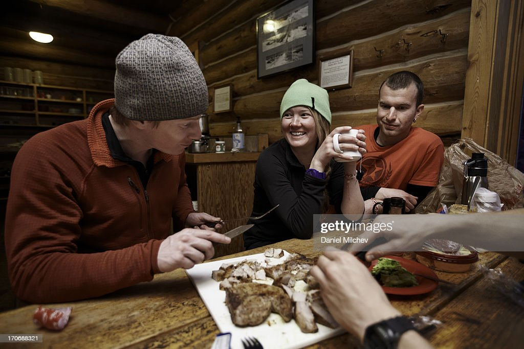 Friends eating food at a mountain hut.