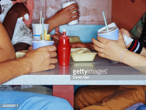 Friends eating food in booth at diner, side view, close up : Stock Photo