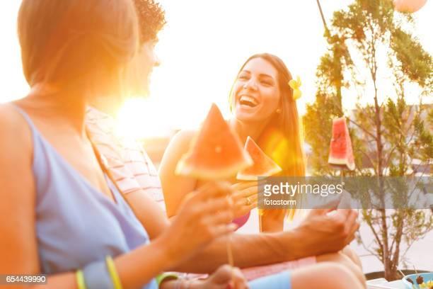 Friends eating healthy snacks on rooftop