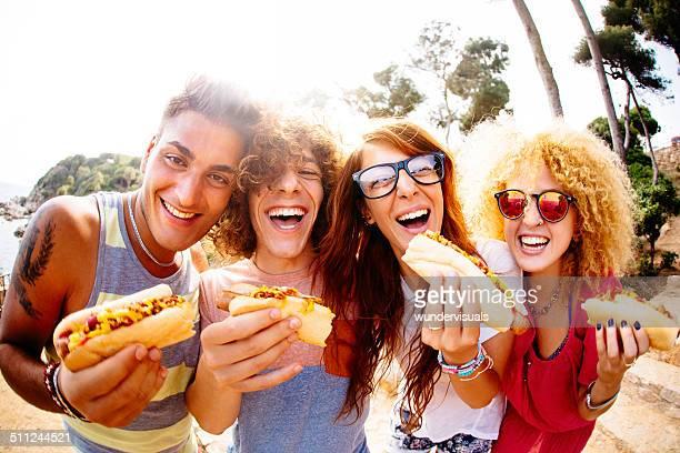 Amigos comiendo perros calientes (hot dogs)