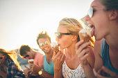 Friends eating icecream on beach