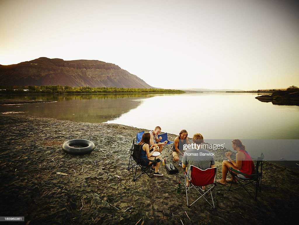 Friends eating in camp chairs near river at sunset : Stock Photo