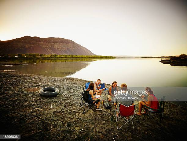 Friends eating in camp chairs near river at sunset