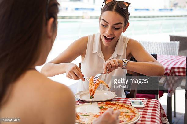 Friends eating Pizza in a sidewalk restaurant