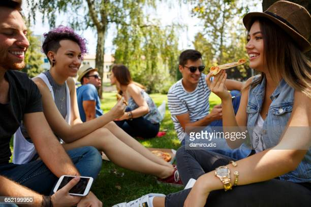 Friends eating pizza outside