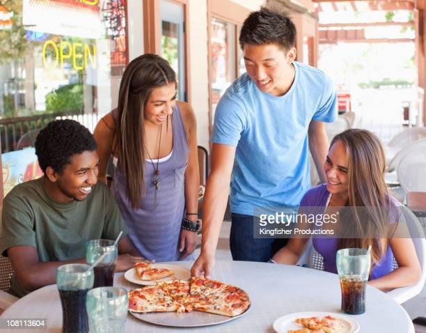 Amici mangiando pizza insieme nel ristorante