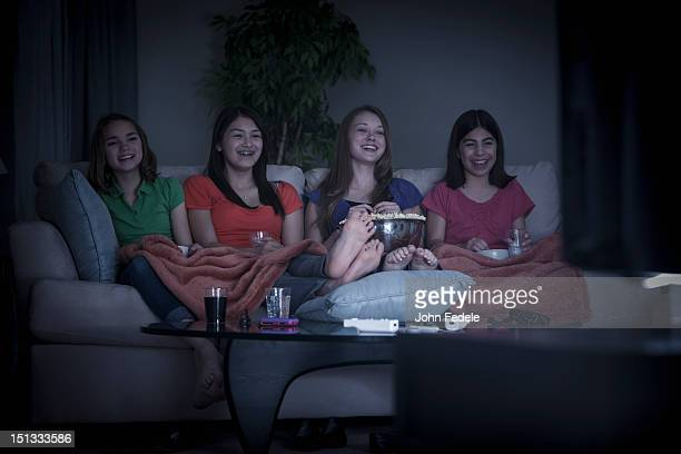 Friends eating popcorn and watching a movie