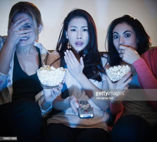 Friends eating popcorn and watching television