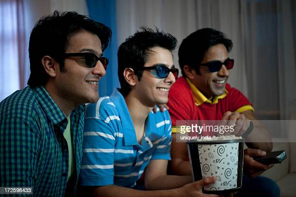 Friends eating popcorns while watching movie with 3-D glasses at home