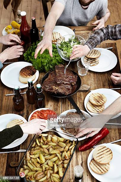 Friends eating potatoes, steaks and meatballs at wooden table