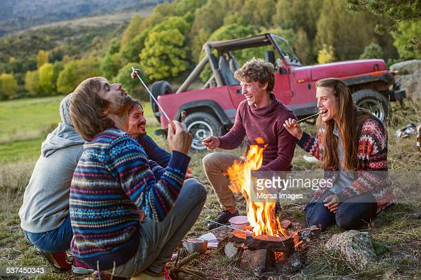 Friends eating roasted marshmallows at campsite