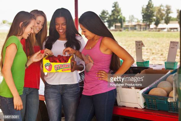 Friends eating strawberries at farm stand