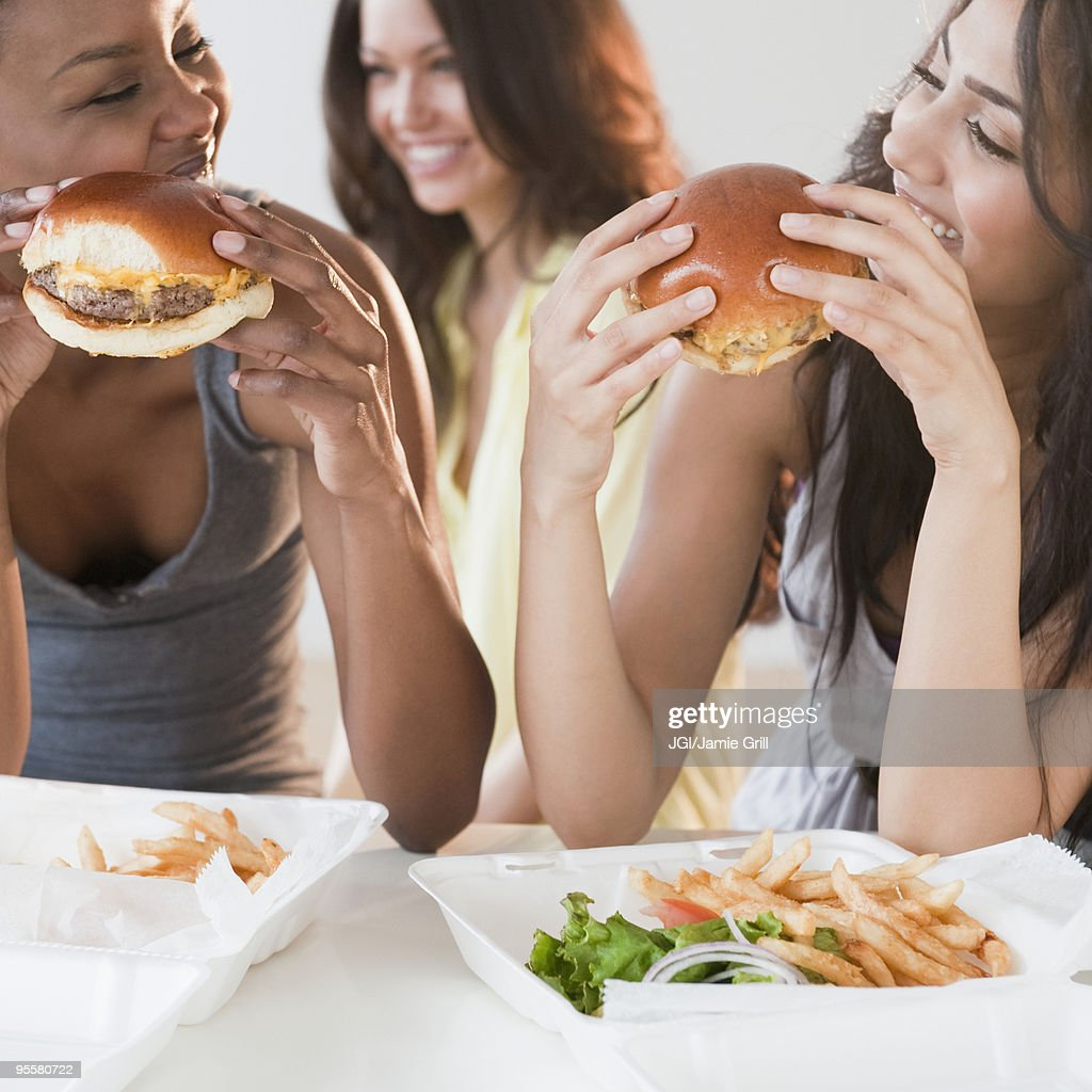 Friends eating take-out hamburgers and french fries : Stock Photo