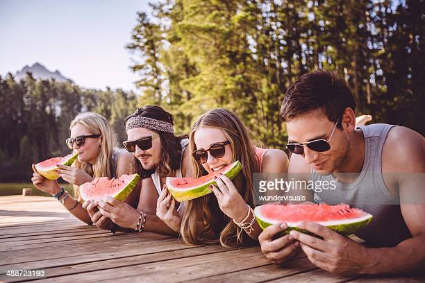 Friends eating watermelon by the lake