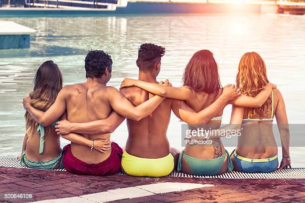 Friends embraced on poolside at sunset