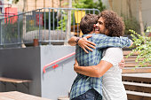 Cheerful best friends embracing each other outside coffee shop. Two young multiethnic guys hugging each other. Happy smiling best friends meeting each other after a long time with a hug.