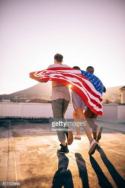 Friends embracing wrapped with an American flag on rooftop