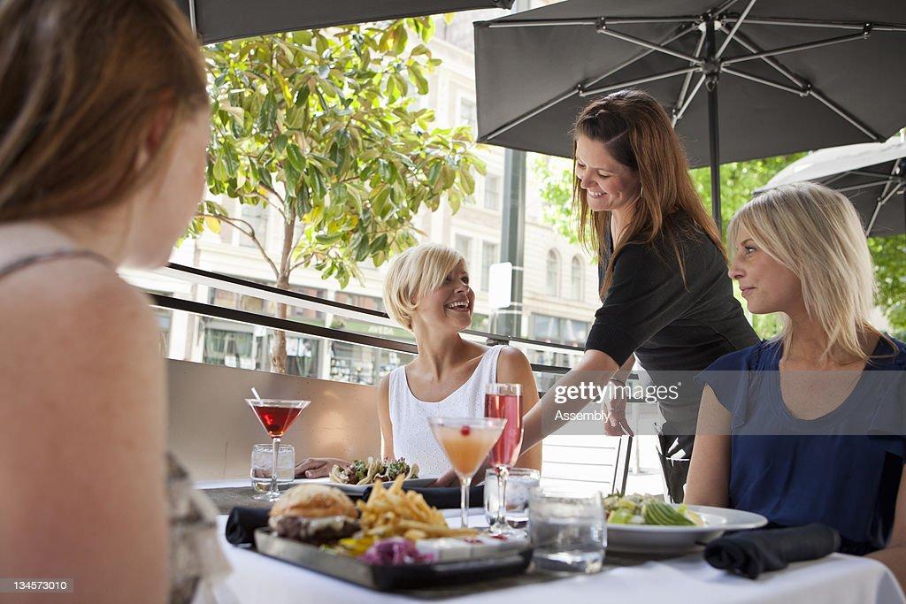 Friends enjoy a meal on a restaurant patio. : Stock Photo