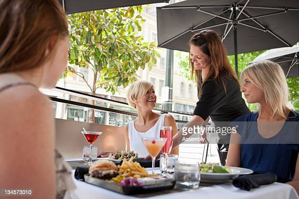 Friends enjoy a meal on a restaurant patio.