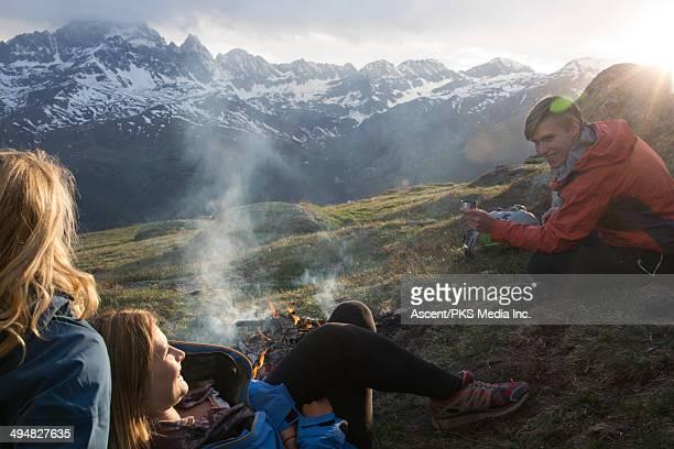 Friends enjoy campfire in mountain meadow