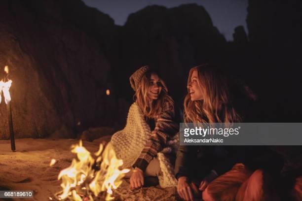 Freunde am Abend am Strand vor dem Kamin genießen