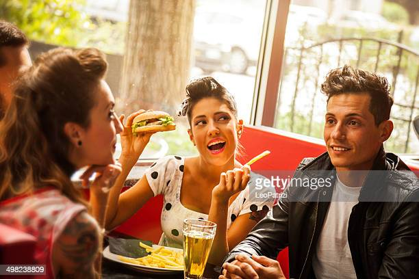 Friends enjoy together dinner in a cafe