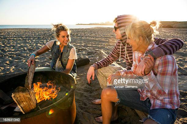 Friends enjoying a beach bonfire.