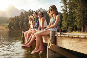 Portrait of group of young people sitting on the edge of a pier, outdoors in nature. Friends enjoying a day at the lake.