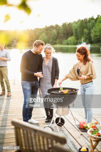 Friends enjoying barbecue party on pier