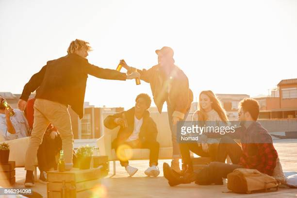 Friends enjoying beer on terrace during summer