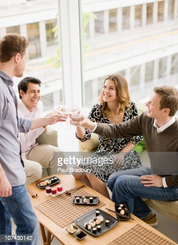 Friends enjoying cocktails and sushi at party : Stock Photo