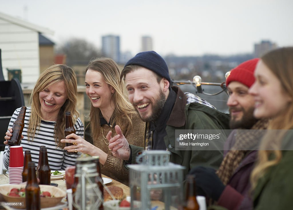Friends enjoying company at table in roof garden. : Stock Photo