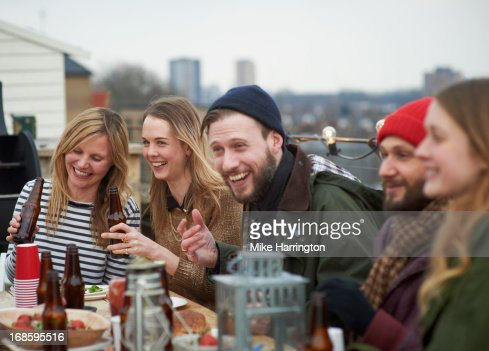 Friends enjoying company at table in roof garden. : Foto de stock