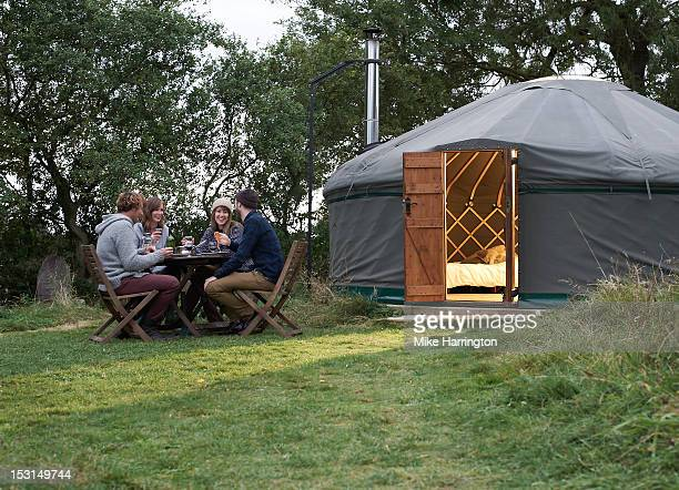 Friends enjoying company over dinner outside yurt.