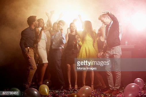 Friends enjoying drinks on dance floor