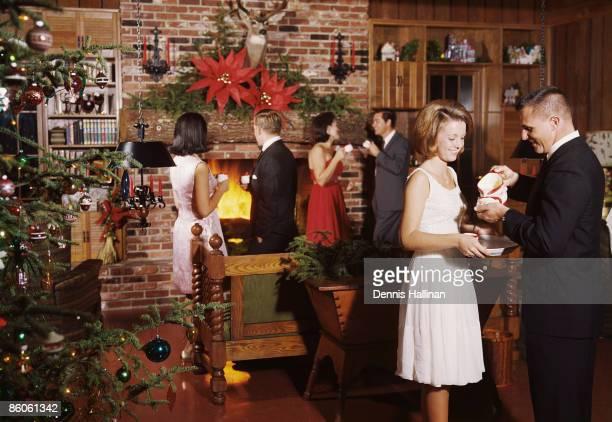 Friends enjoying eggnog and talking at Christmas party
