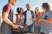 Young multiethnic friends having fun grilling meat enjoying bbq party. Group of happy guys and girls cooking and eating at barbecue dinner outdoor. Men and women standing around grill, chatting, drink