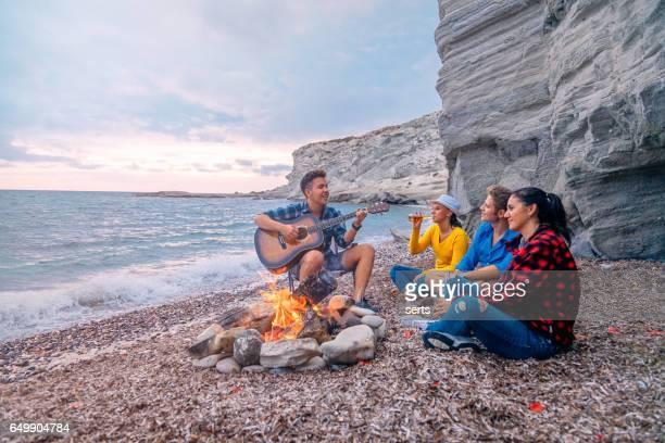 Amis appréciant la musique près du feu de camp