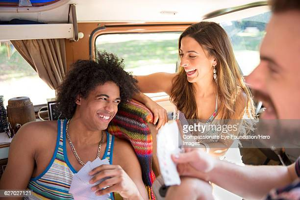 Friends enjoying playing cards in camper van