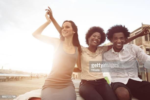 Friends enjoying road trip along the Malecon