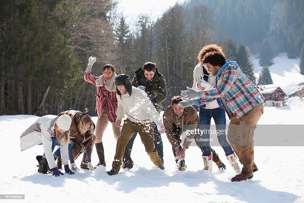Friends enjoying snowball fight in field : Stock Photo