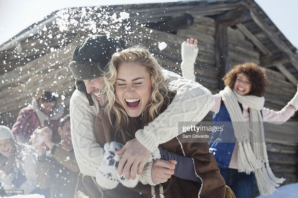 Friends enjoying snowball fight : Stock Photo