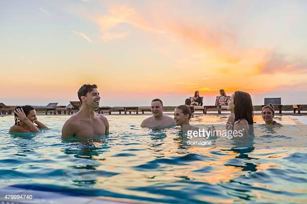 Amici godere la festa in piscina in estate