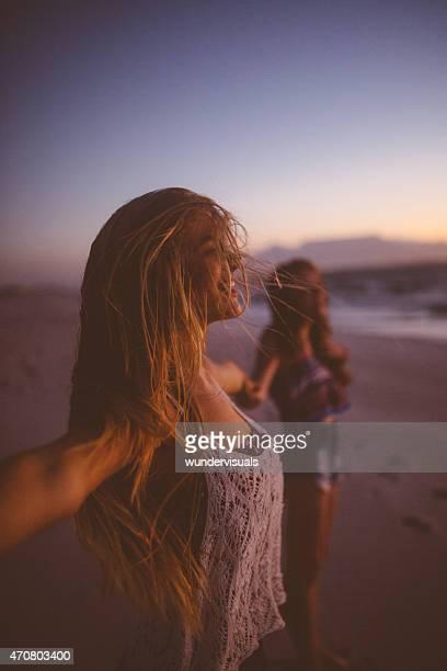 Freunde genießen Freiheit am Strand in der Dämmerung