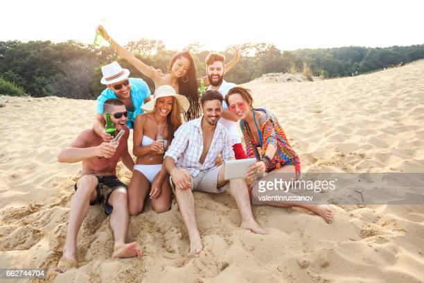Friends enjoying vacations and making selfie on beach