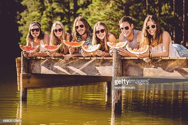 Amis appréciant la pastèque sur la jetée